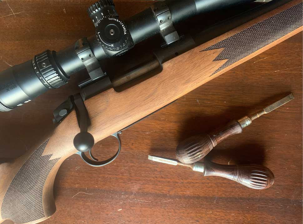 A rifle on a table next to wood handle repair tools.