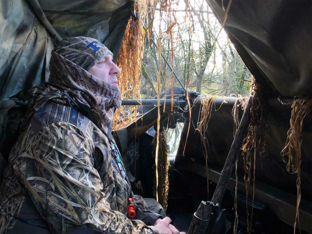 A hunter in full camo sits in a hunting blind while gazing out the window.