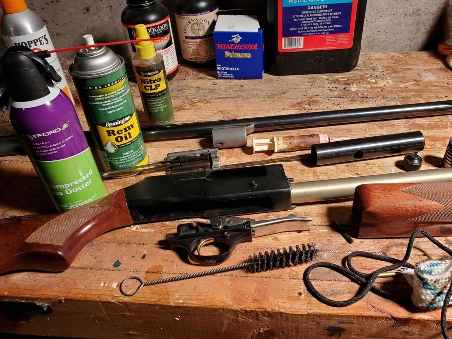 A disaassembled shotgun on a table next to cleaning supplies and tools.