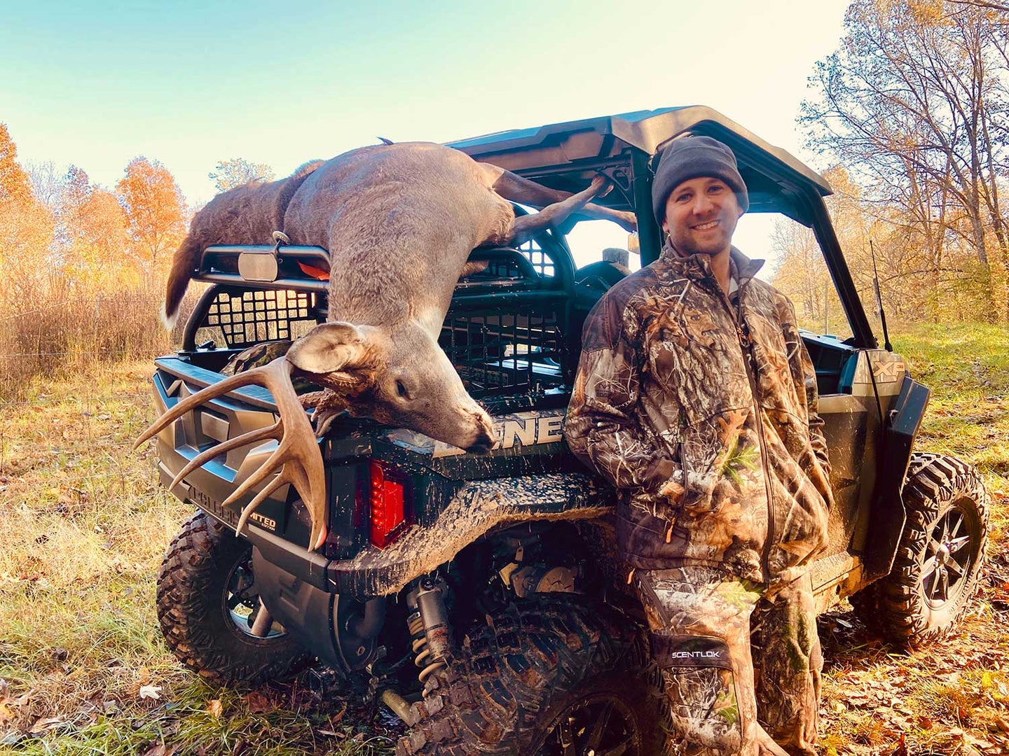 A hunter stands beside a Polaris General UTV with a dropped whitetail deer on the tailgate.