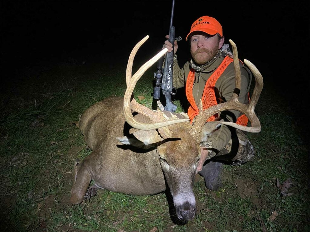 A hunter kneels behind a large whitetail buck and holds its head near the antlers.