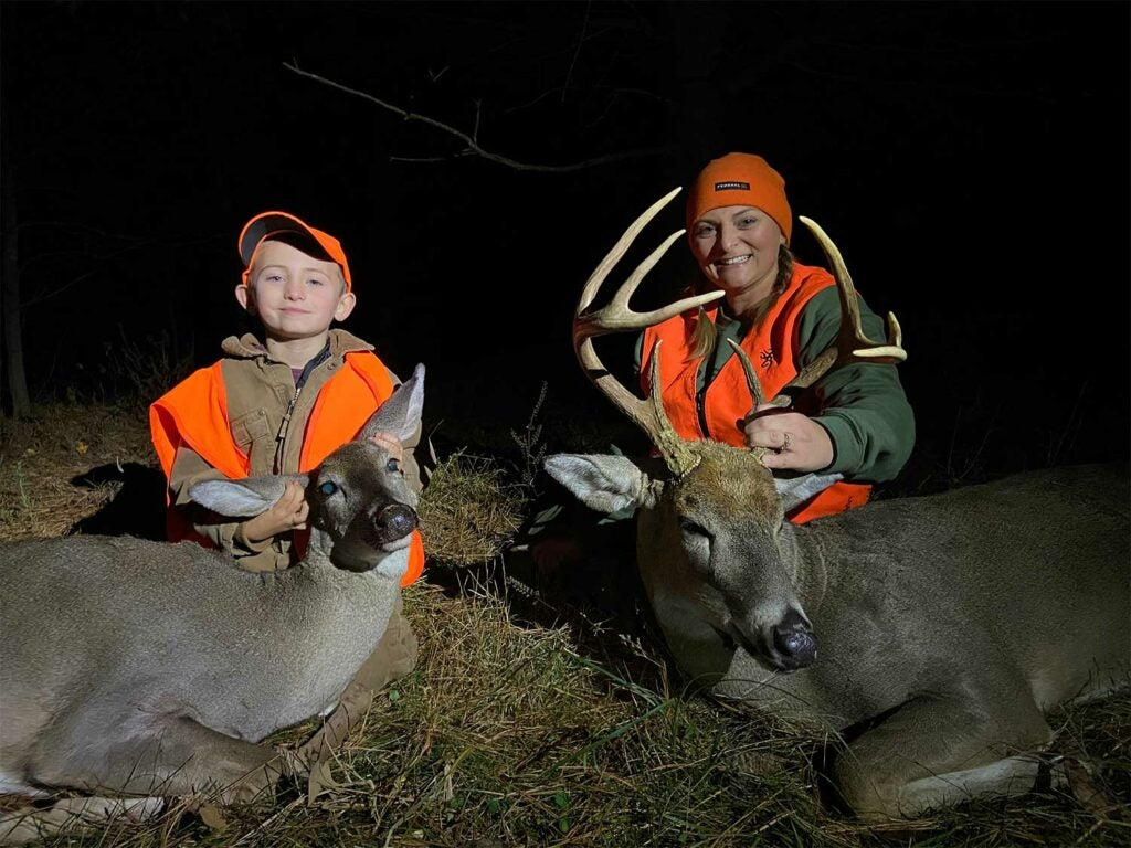 A woman and young boy kneel behind dropped deer.
