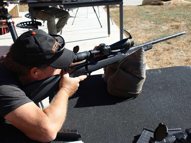 A shooter aims a rifle at a shooting range.