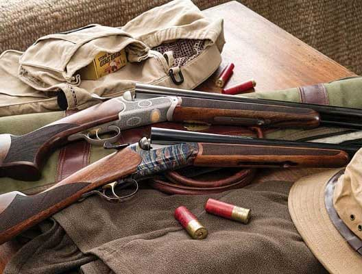 Two shotguns on a hunting jacket and backet.