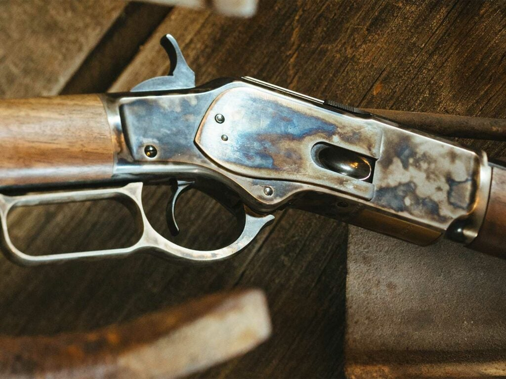 A close up detail of the metalwork on a lever-action rifle.