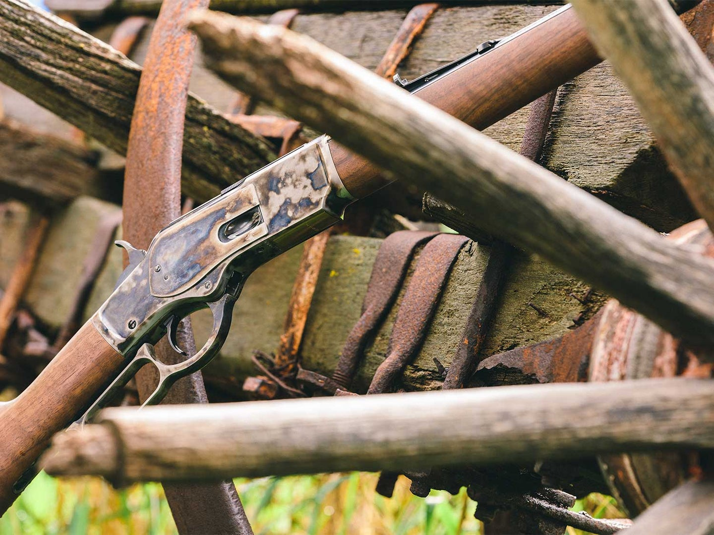A Winchester rifle leaning against a wooden wagon.