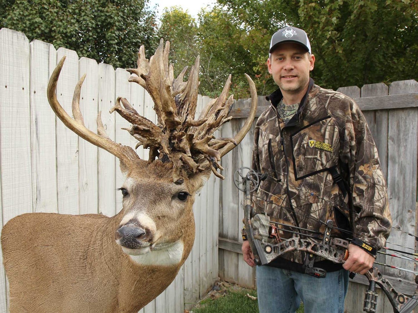 A hunter standing next to a large whitetail buck with a nontypical antler spread.