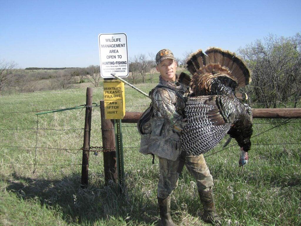 A hunter next to a large public land turkey.