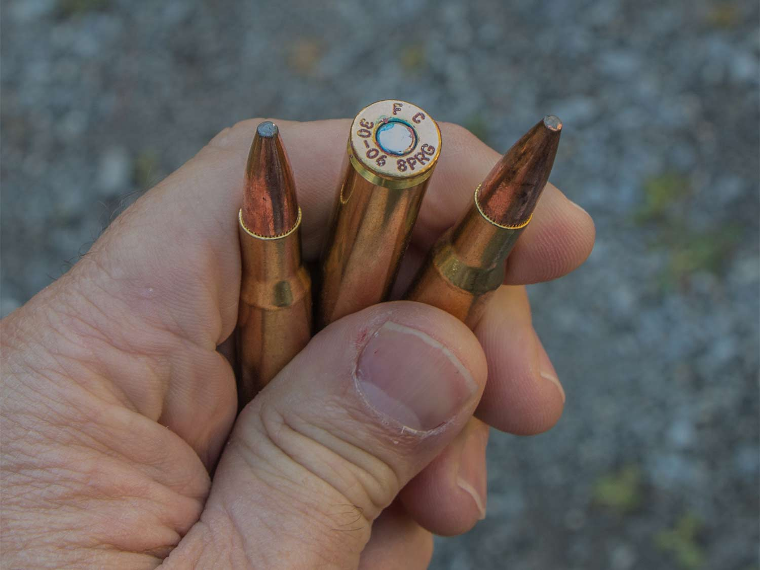 A hand holds three rifle bullets.