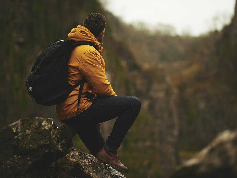 Man sitting on trail wearing hiking backpack