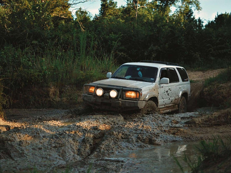 A white truck riding through deep muds.
