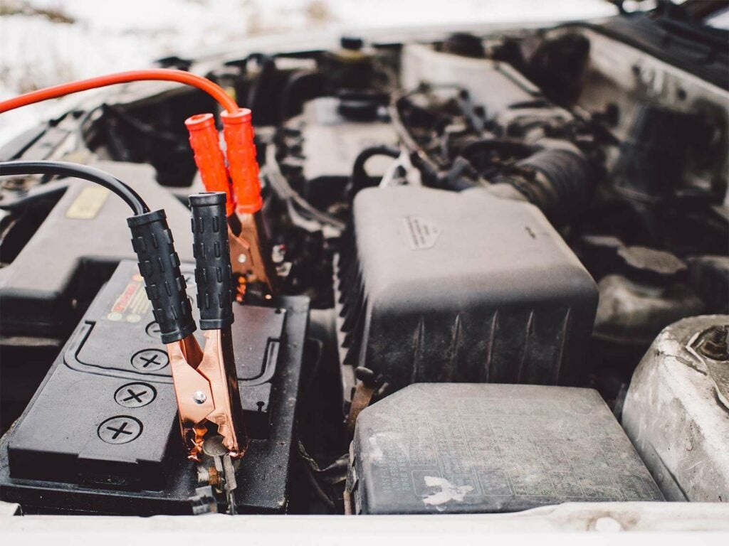 Jumper cables hooked up to the battery in a truck engine.
