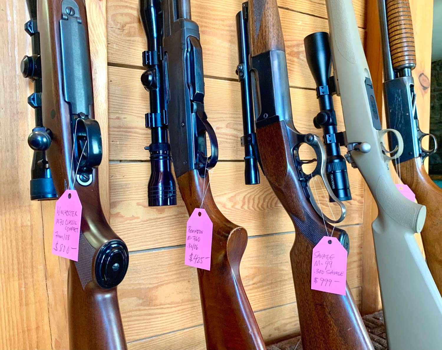 A lineup of rifles tagged with sales tags.