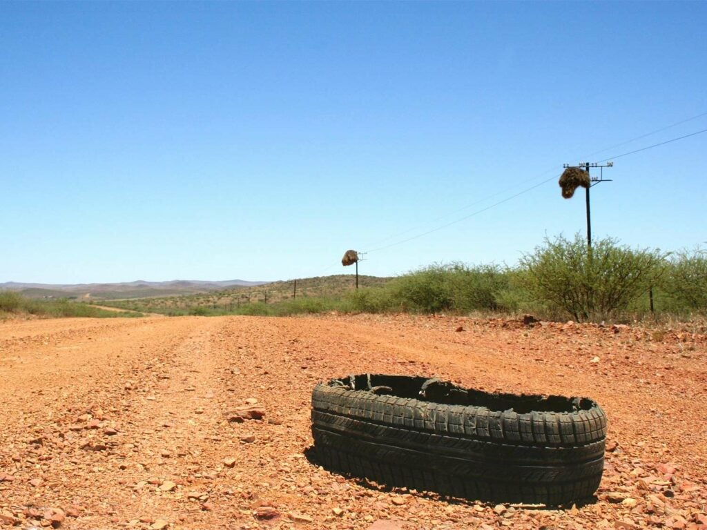 A blown out tire on the side of a dirt road.