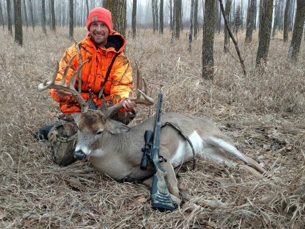 A hunter kneels beside a large deer and holds its head by the antlers.