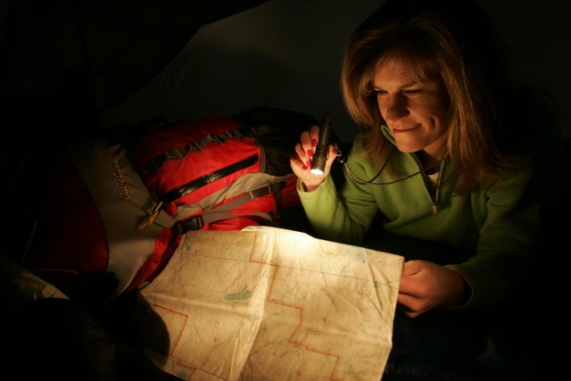 Woman shining a flashlight on a map