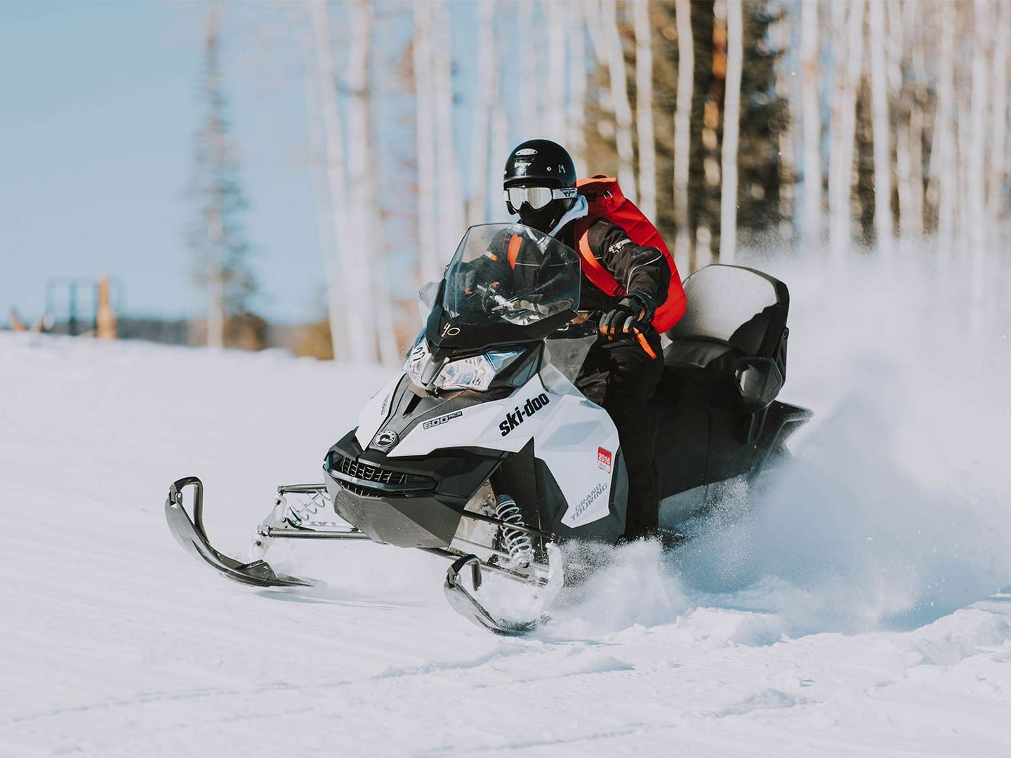 A person riding a snowmobile with the best snowmobile helmet.