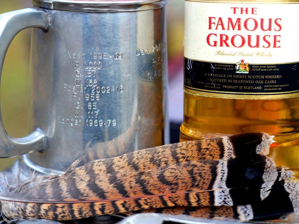 Feathers next to a bottle of scotch.