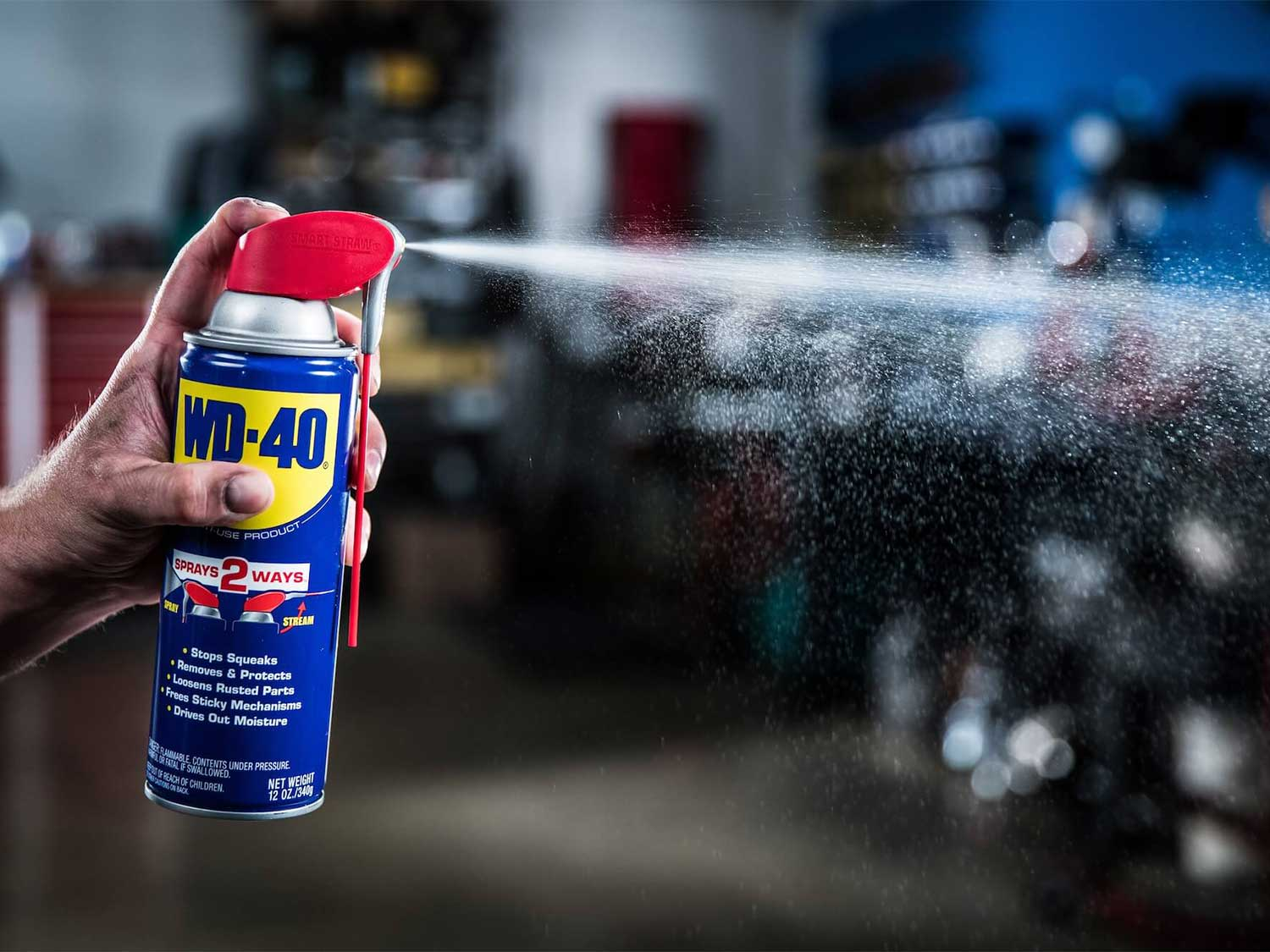 A person spraying a can of WD40 in a garage.