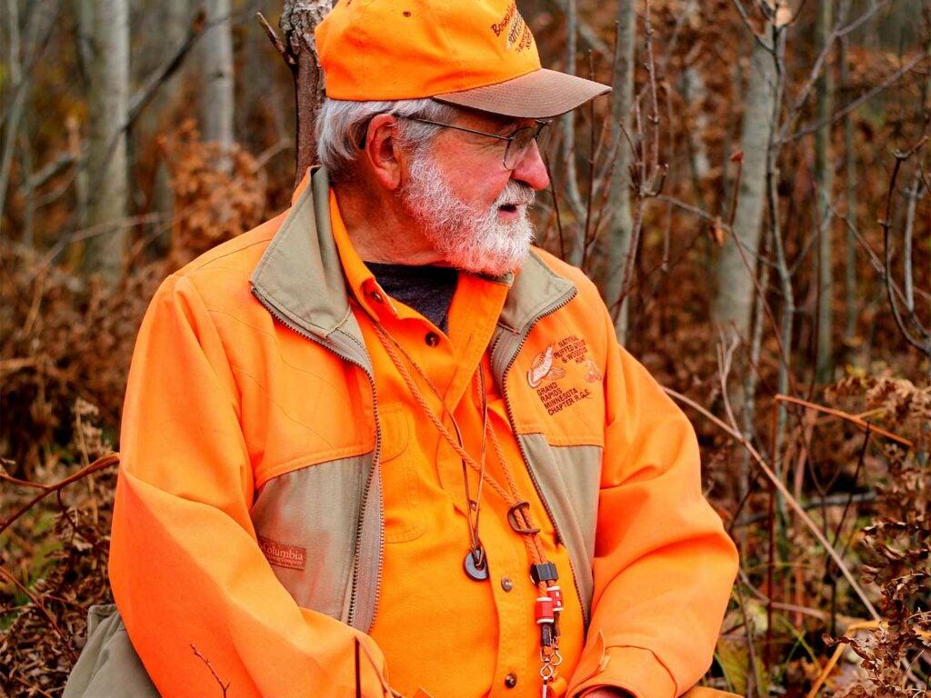 A hunter wears hunter orange in the woods.