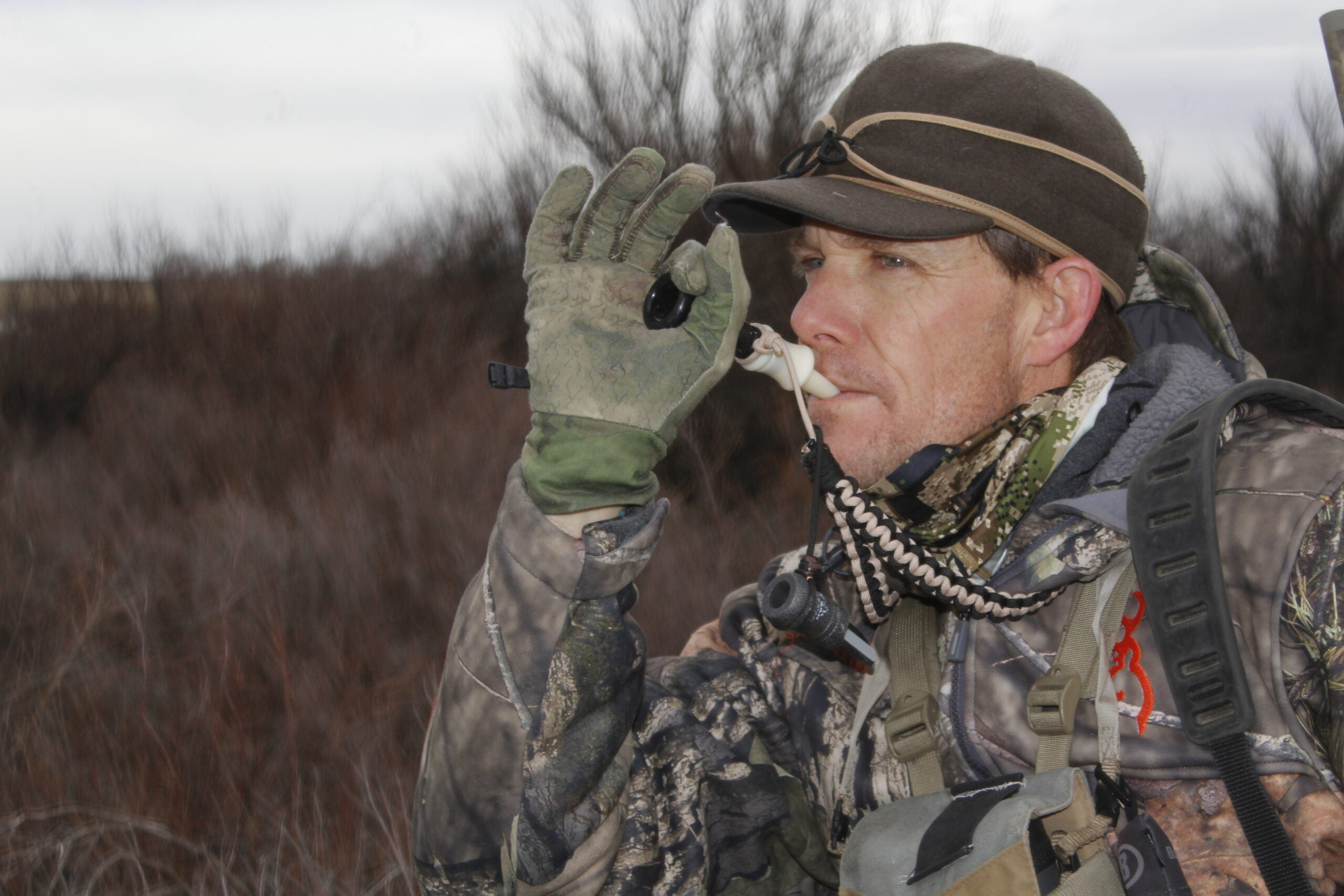 Hunter wearing camouflage blowing on a coyote call.