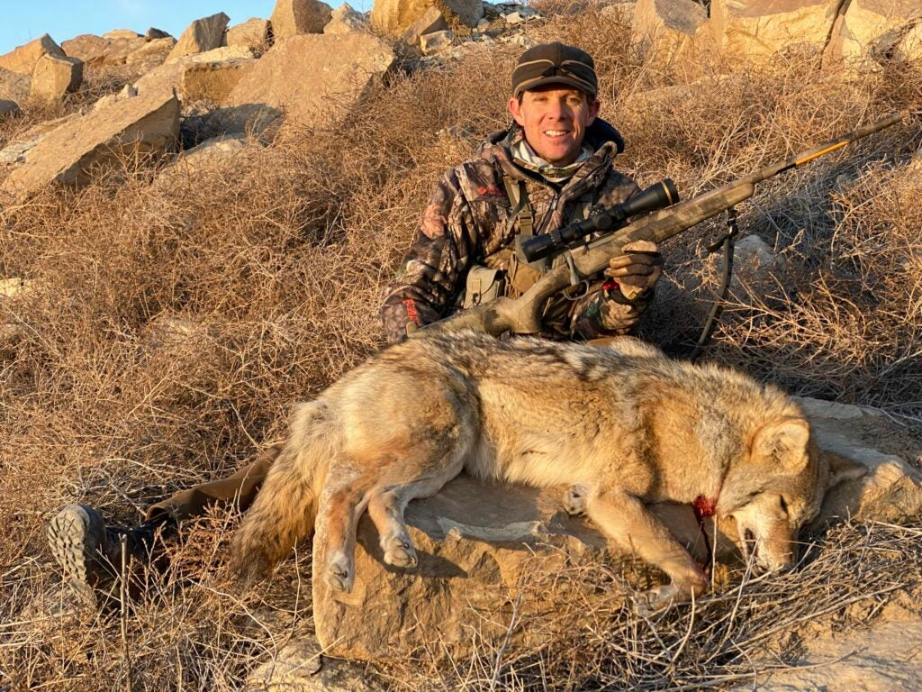 Hunter in rocky terrain holding a rifle and sitting behind a dead coyote.