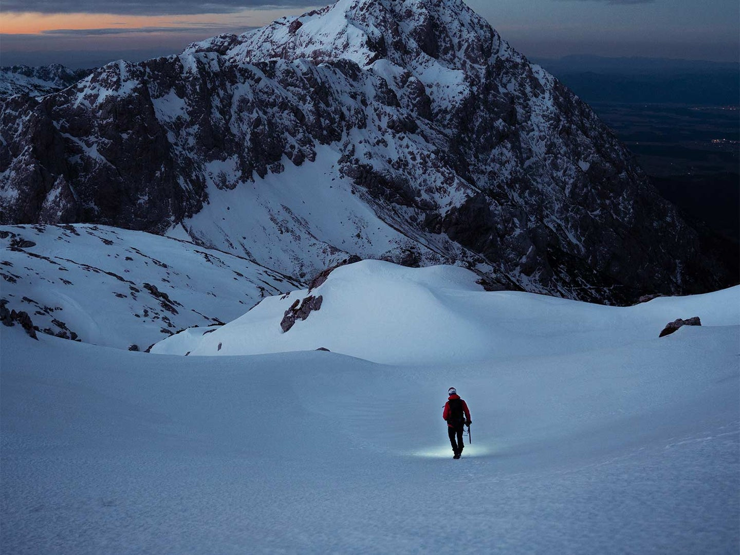 A person walks through the snow on the mountain side.