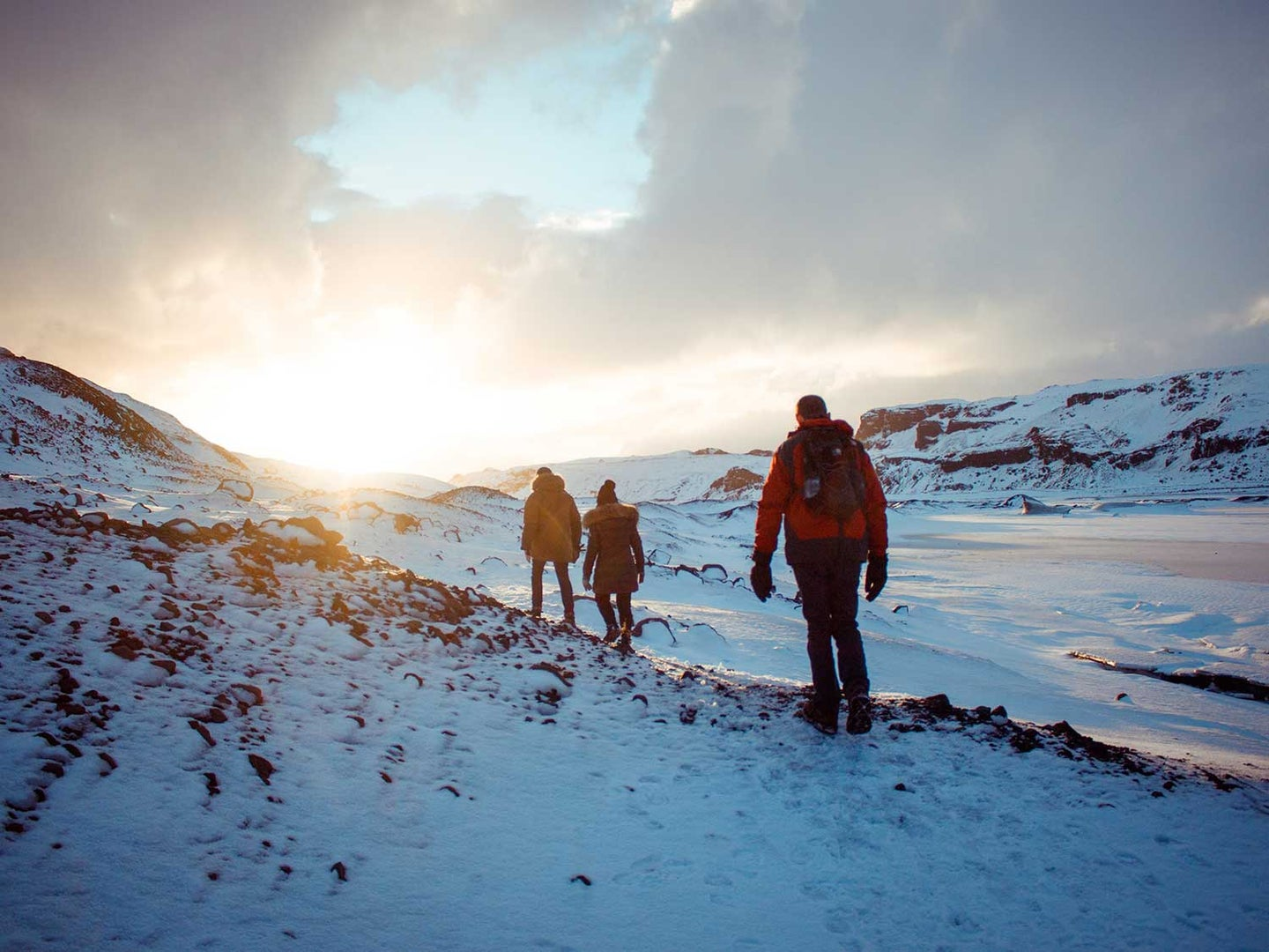 People hiking through snowy mountains.