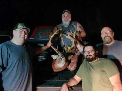 Four hunters next to a giant buck.