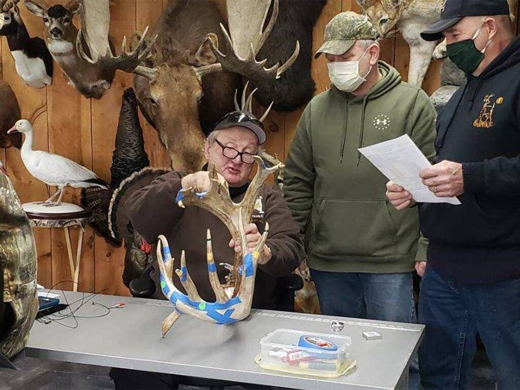 Hunters stand beside a person measuring deer antlers.