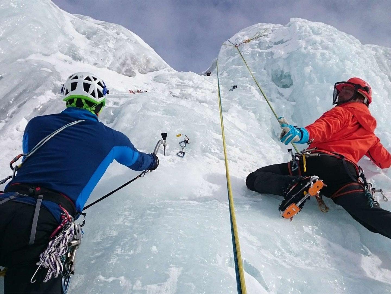 Two ice climbers climb up a wall.