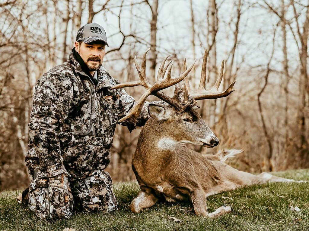 A hunter kneels behind a large whitetail buck and holds its head by the antlers.