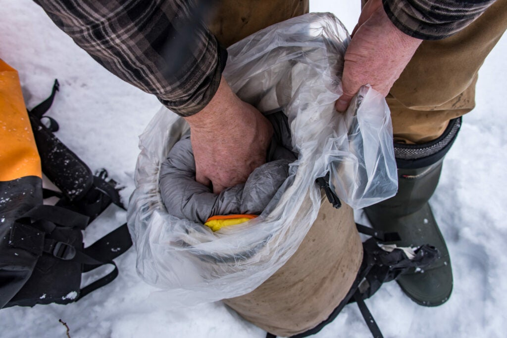 Keep a sleeping bag dry by lining a plastic bag in a compression sack.