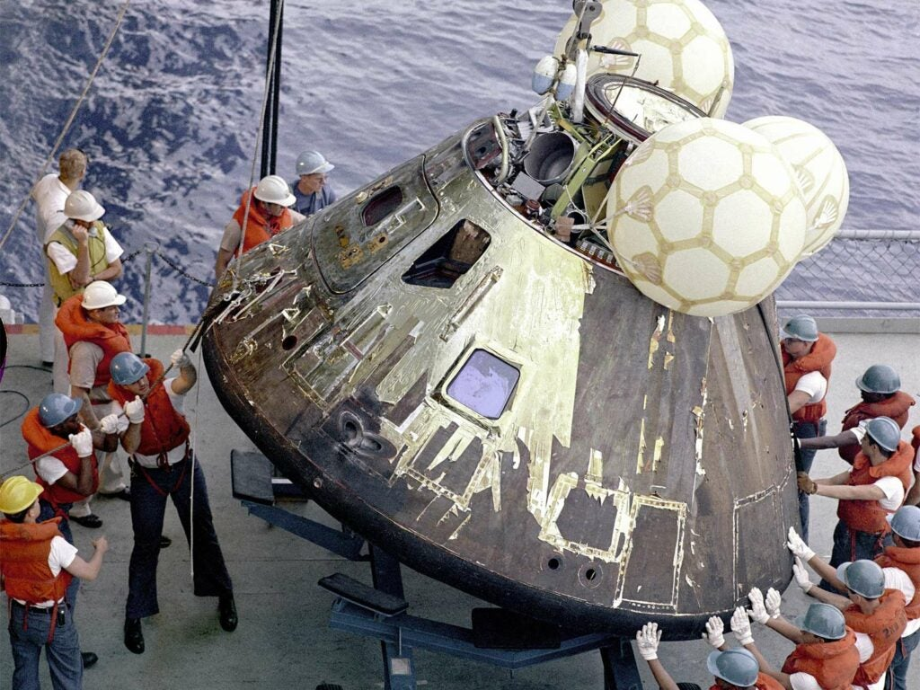 A group of people standing around the Apollo 13.