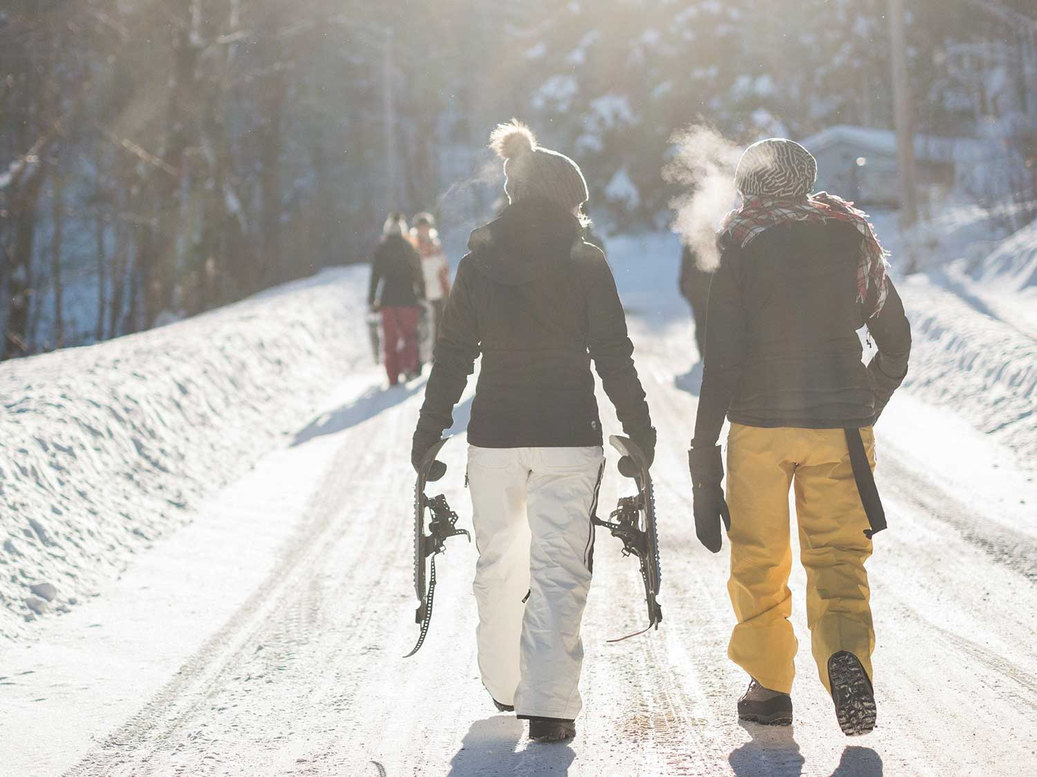 Man and woman hiking while carrying snowshoes and wearing long underwear to stay warm.