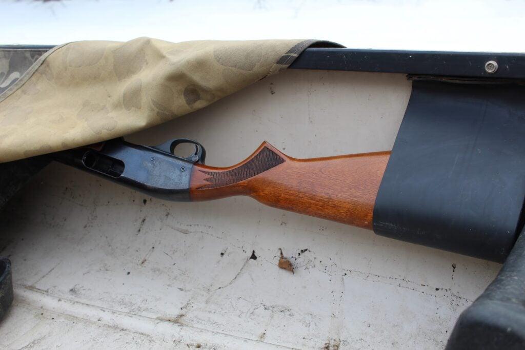 Canvas covering shotgun in canoe gun rack.