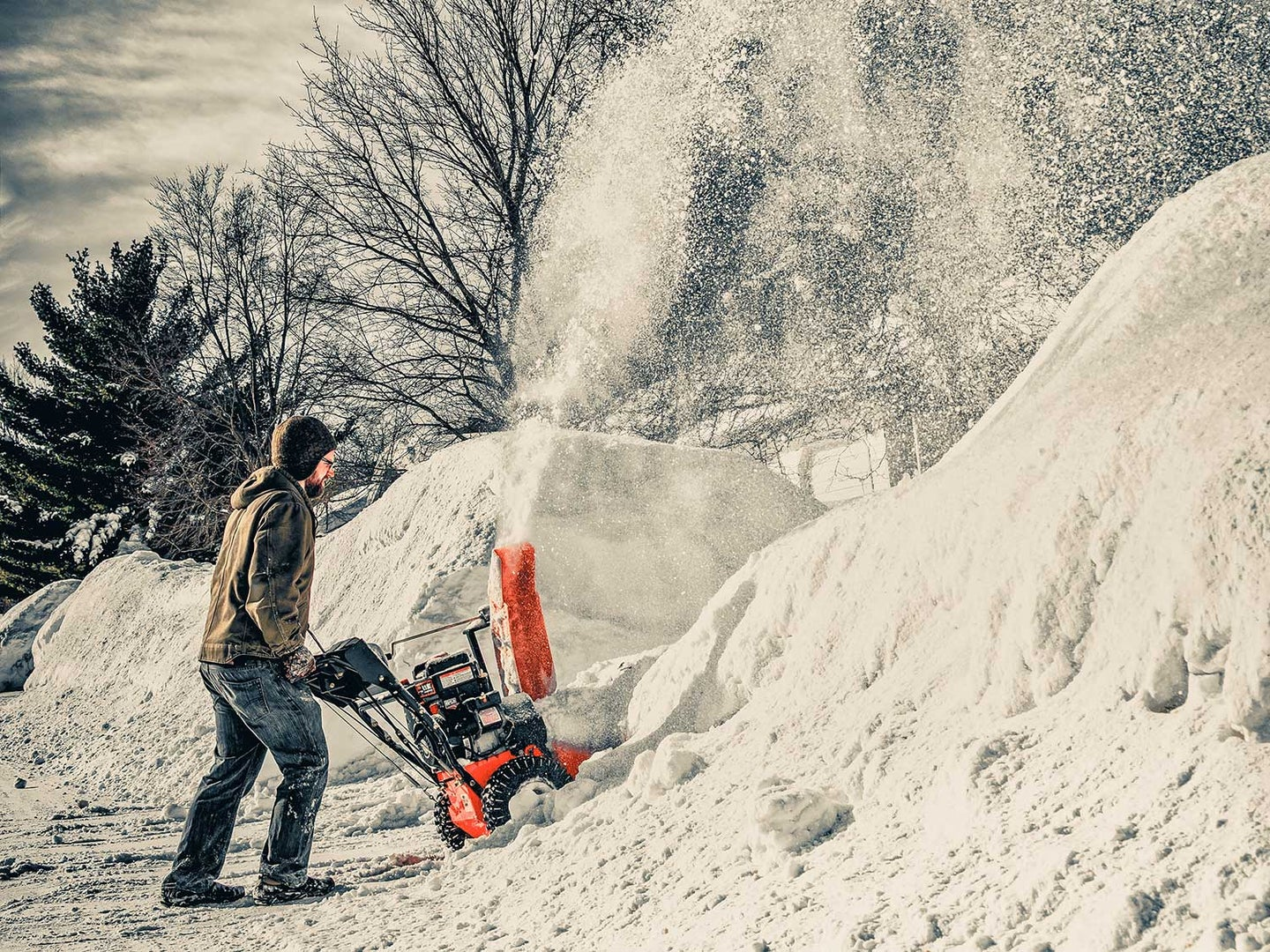 Man using snow plow keeping hands warm with heated gloves.