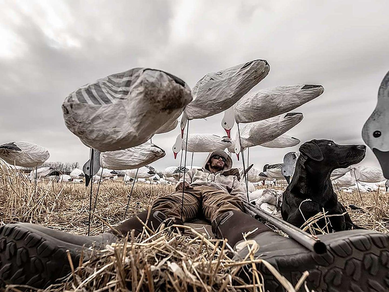 A hunter amogst goose decoys.