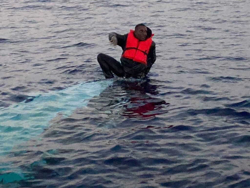 A man sits stranded on a capsized boat at sea.