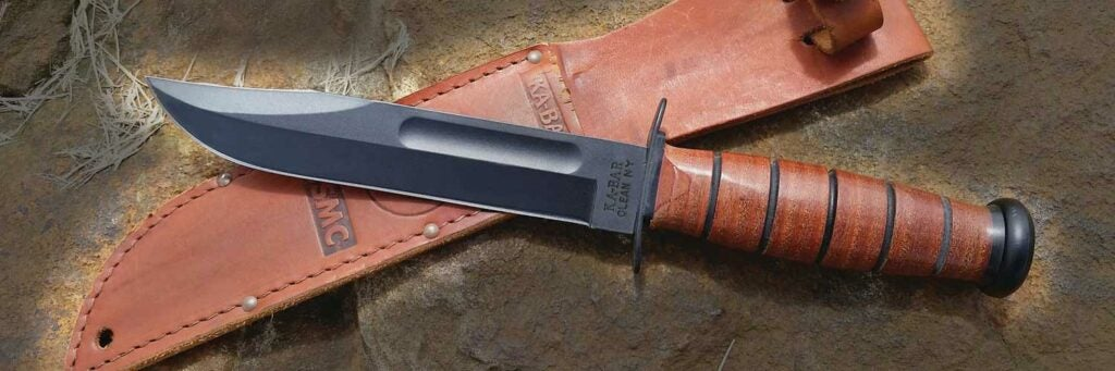 A knife and leather sheath on a rock ground.