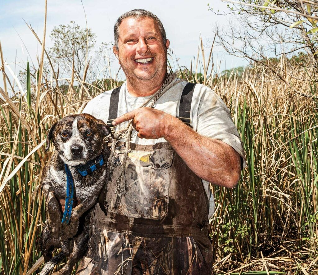 Hunter holding a bluetick hunting dog.