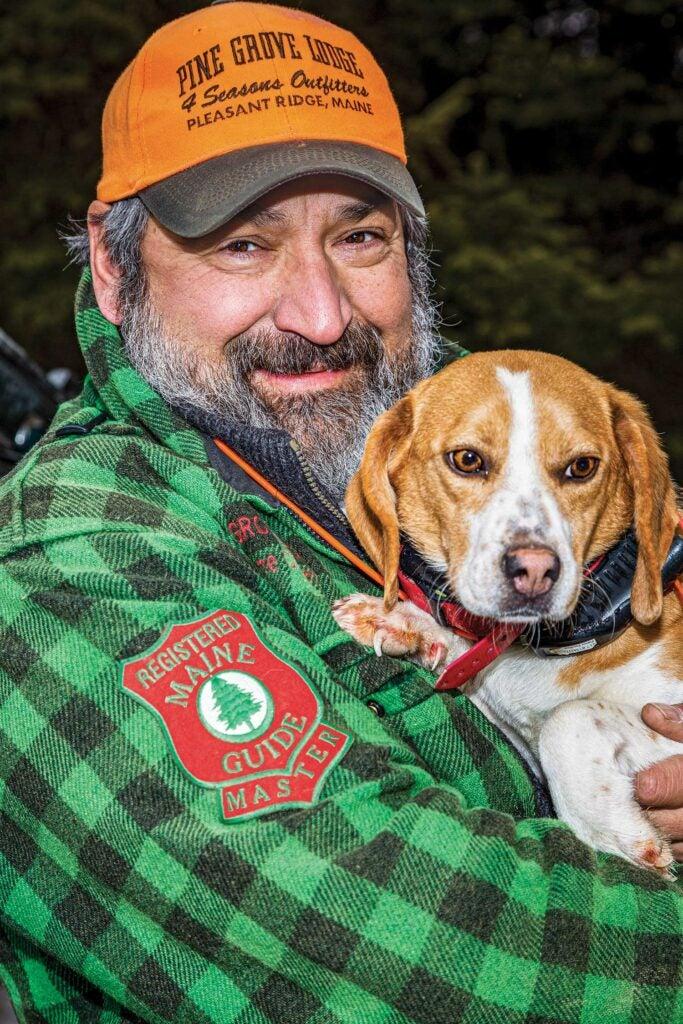 Hunter holding a beagle.