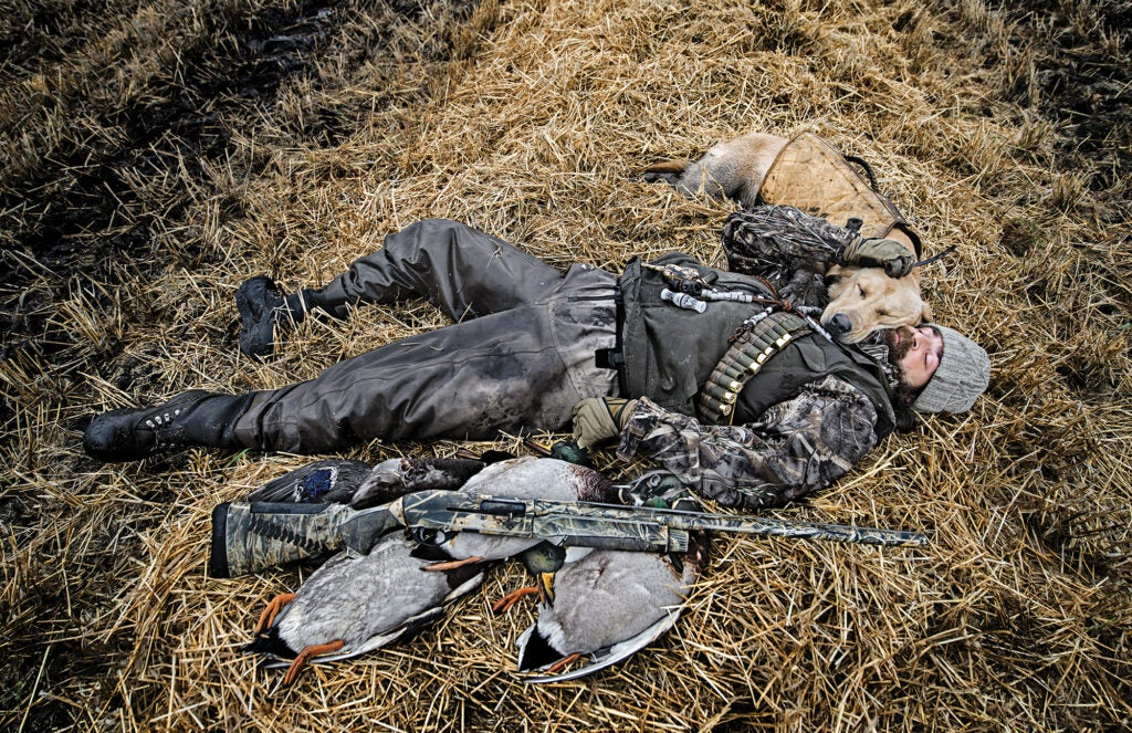 Hunter lying on the ground with his hunting dog.