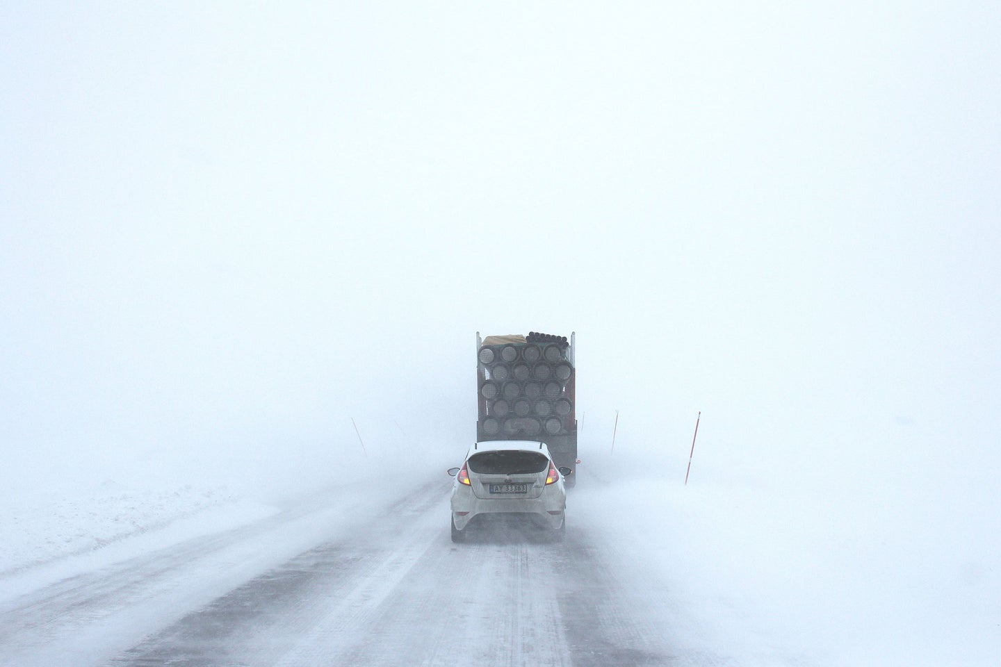 Car driving on a snowy road with the best snow tires.