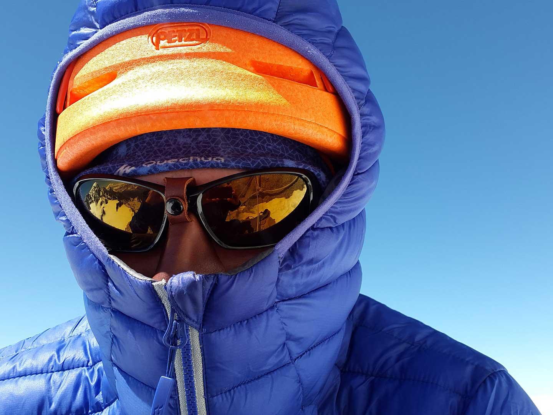 Person wearing a blue parka, orange hat, and glacier glasses.