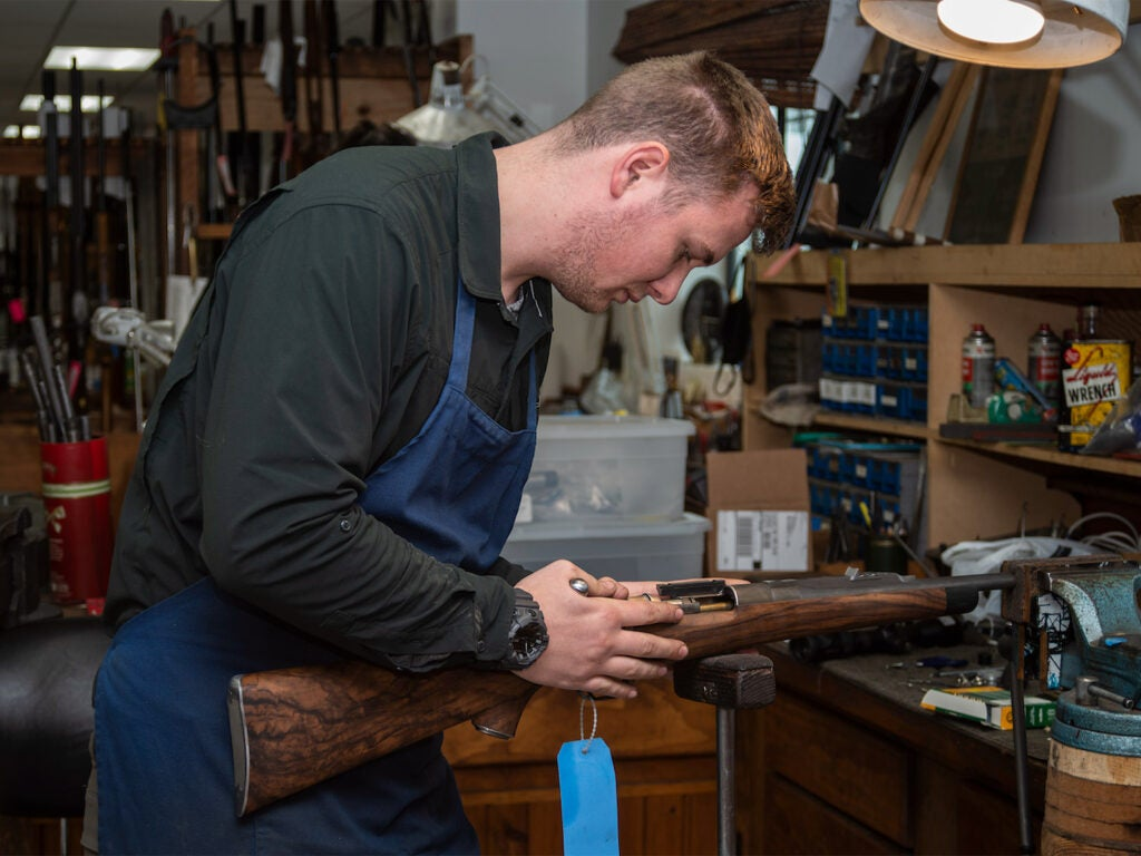 A man working on the stock of a rifle.