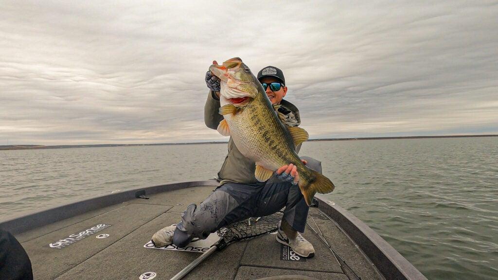 Man on boat in lake holding big largemouth bass.