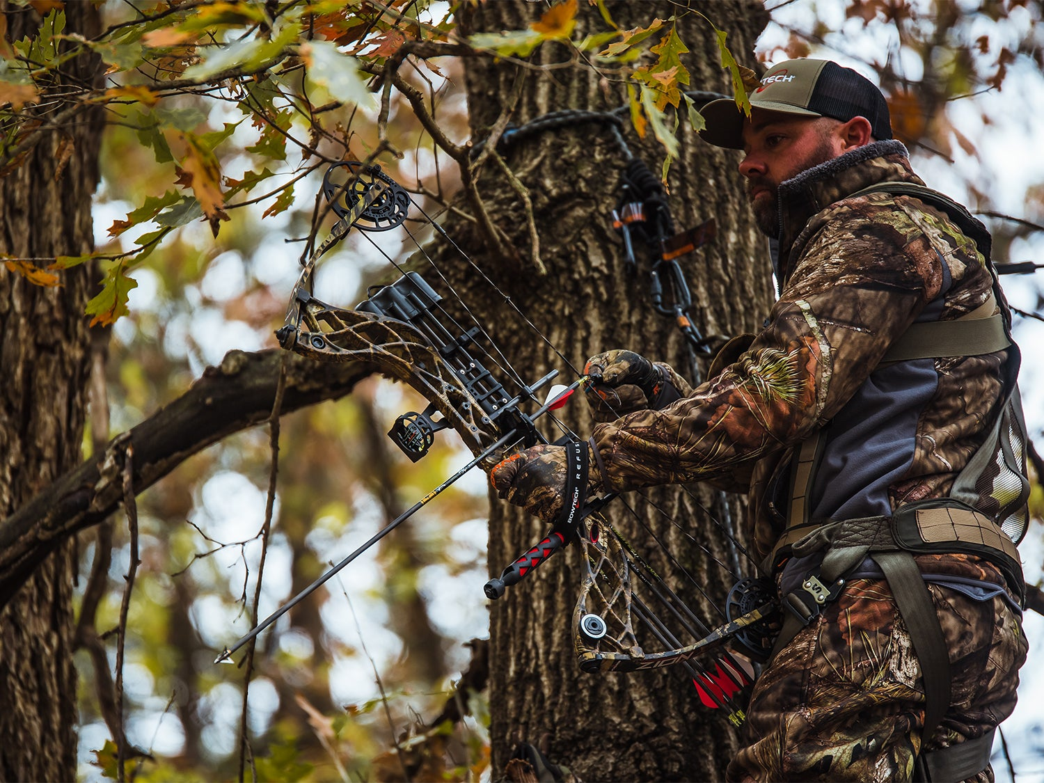 A hunter stands in a treestand and holds a compound bow.