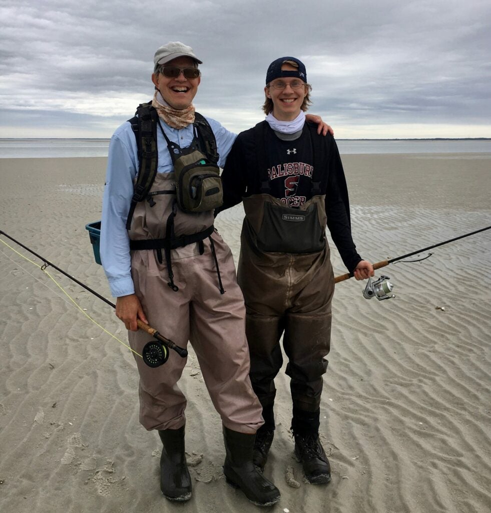 Two fishermen standing on the beach.
