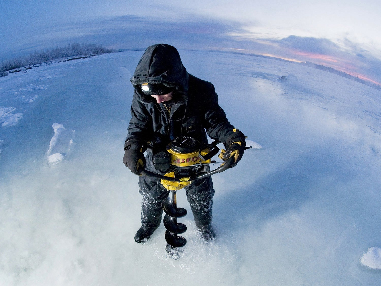 A man uses an ice auger to drill through the ice, while wearing the best heated jacket.
